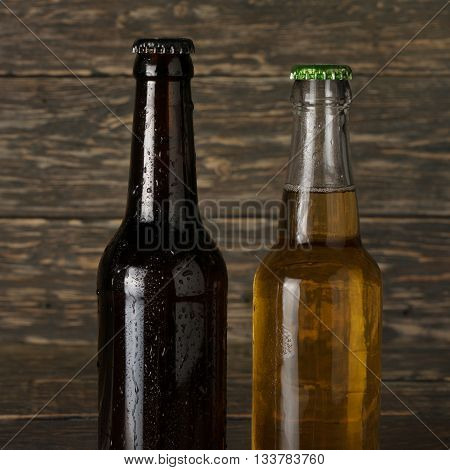 Two wet cold bottle of beer closeup on a dark wooden background. Light and dark beer on dark wooden background