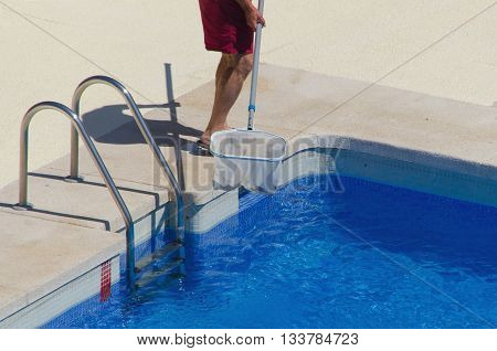 A Man Cleans The Swimming Pool With A Net