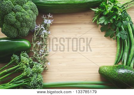 Top flat lay view of fresh organic vegetables on wooden cutting board with copy space