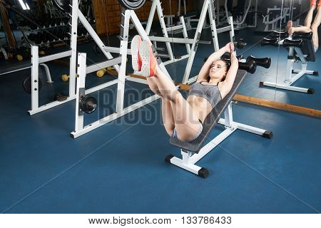 Beautiful young body builder doing exercises on trainer in the gym