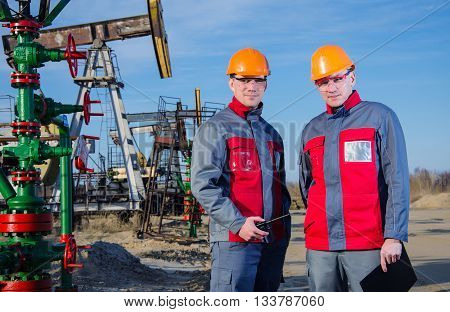 Workers in the oilfield one holding radio in his hand. Pump jack and wellhead background. Oil and gas concept.