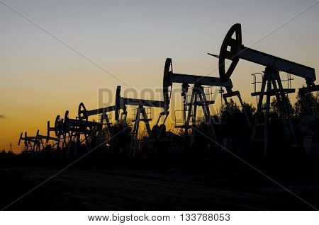 Pump jacks silhouettes during sunset on the oilfield. Oil and gas concept.