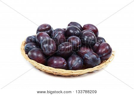 Fresh plums in a wooden basket isolated on white background.