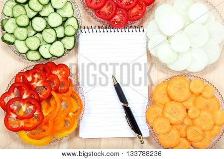 Notebook for recipes and vegetables on wooden table.
