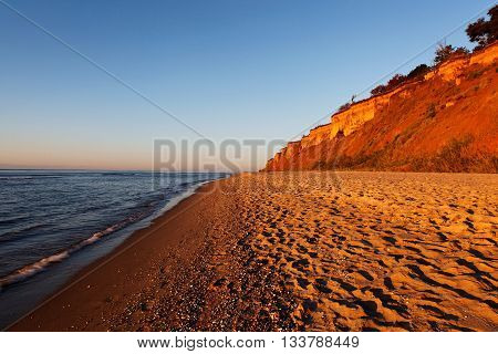 Sea with a sandy beach and sky in the rays of the rising sun.
