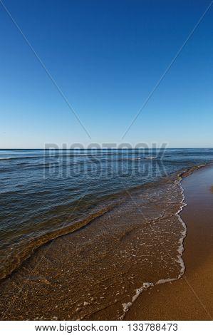 Sea with a sandy beach and blue sky.