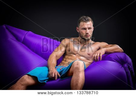 Handsome bearded topless man with tattoo looking away thoughtfully while sitting on purple air chair