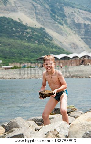 boy with wet stone standing near the sea