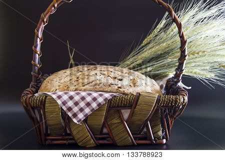 Vintage style: Homemade gluten-free and without yeast artisan bread in a wicker basket with ears of barley wrapped in a plaid napkin