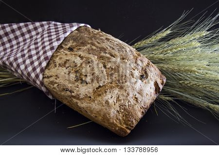 Homemade gluten-free and without yeast artisan bread with ears of barley wrapped in checkered napkin