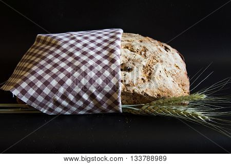 Artisan bread closeup with ears of wheat on black background