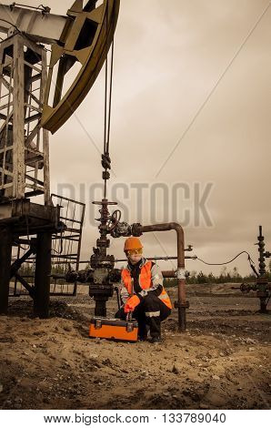 Woman engineer in the oil field repairing wellhead with the wrench wearing orange helmet and work clothes. Pump jack and wellhead background. Oil and gas concept.