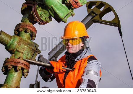 Woman engineer in the oil field repairing wellhead with the wrench wearing orange helmet and work clothes. Pump jack background. Oil and gas concept.