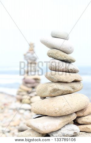 Under exposed image. Building towers with stones on the pebble beach on the Holy Island of Lindisfarne, Northumberland, England, UK, stones and sea