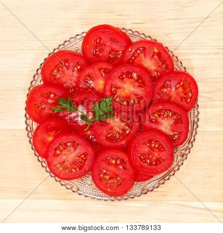 Fresh vegetable tomato slices in a glass dish isolated on a white background.
