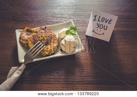 Healthy breakfast prepared with love: Fritters of cottage cheese with greens in heart shape with sour cream and a note - I love you
