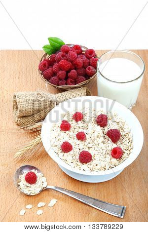 Fresh raspberries Oatmeal flakes and milk on a wooden table. Healthy food.