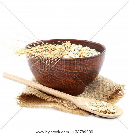 Oatmeal flakes in wooden bowl isolated on white background. Healthy food.