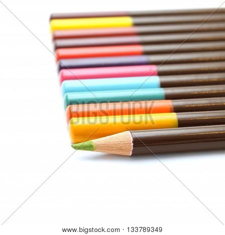 Colored pencils and a unique green on a white background