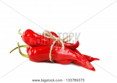 Red hot chili peppers tied with rope isolated on white background.