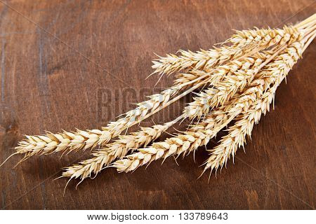 Wheat ears on the a wooden background.