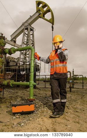 Woman engineer in the oil field talking on the radio wearing orange helmet and work clothes. Pump jack background. Oil and gas concept. Toned.