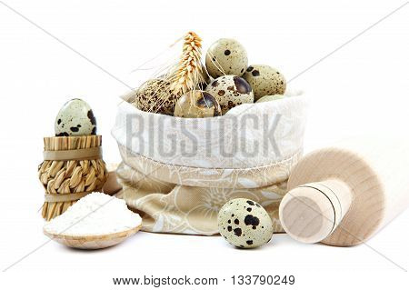 Quail eggs in a canvas bag and flour in a wooden spoon isolated on white background.