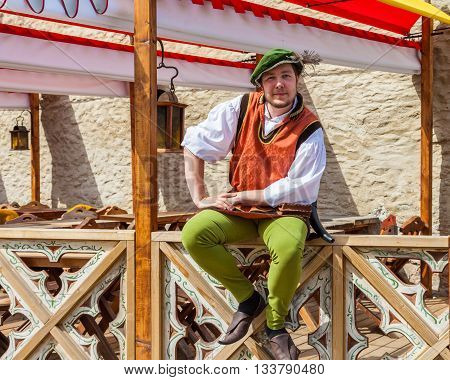 Tallinn Estonia - June 2 2016: cheerful man in national medieval clothing near medieval restaurant in the Historical Center of Tallinn city. Tallinn Estonia.