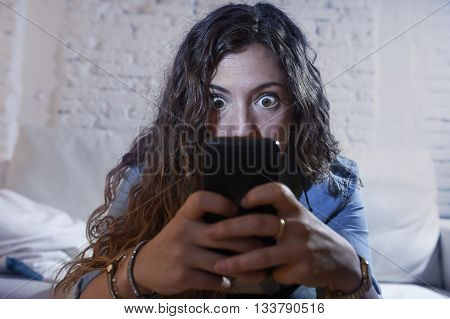 young hispanic woman holding mobile phone looking in crazy eyes social network addict face expression at home couch in telephone addiction and internet overuse concept