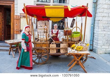 Tallinn Estonia - June 2 2016: Beautiful girls in national medieval dresses are selling nuts on a wooden cart in the Historical Center of Tallinn city. Tallinn Estonia.