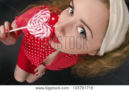 Beautiful young pin-up woman wearing red cloths with radiant red lipstick. Dark background. Fish eye shot.