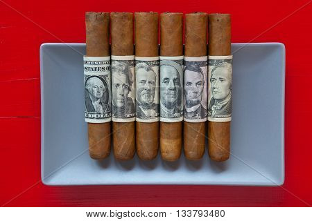 Gray ceramic dish and luxury Cuban cigars with US dollar banknotes on over red background rectangle dish
