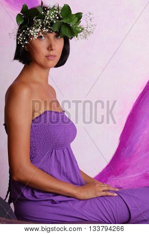 Beautiful sensual woman wearing a wreath of flowers and leaves on a purple background. Series