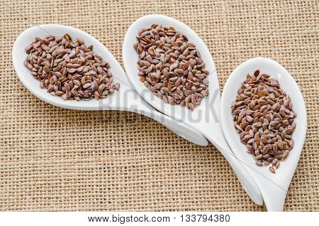 linseed photo of on white spoon on sack background.