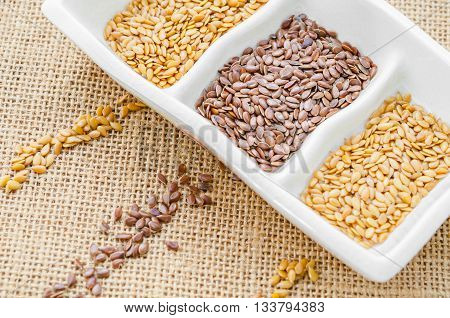 Difference of gold and brown linseeds or flax seeds in white bowl on sack background.