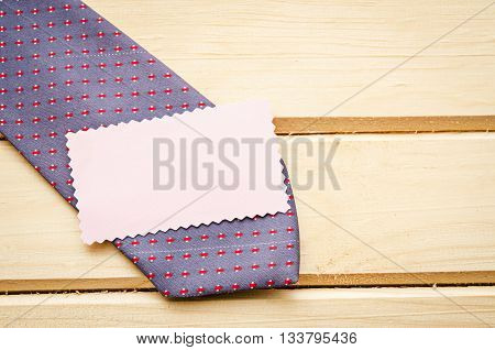 Blank tag with necktie on wooden background ready for your text or message.