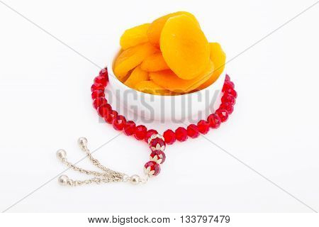 Tasty dried apricots in a white plate with a red rosayr around for breakfast in Ramadan