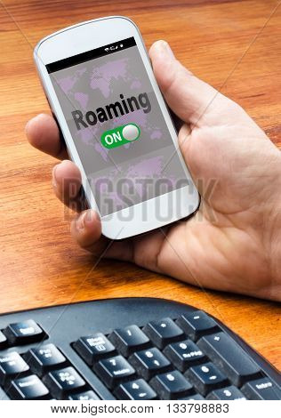 Man's hand holding a white mobile with roaming on words and world map background on the screen