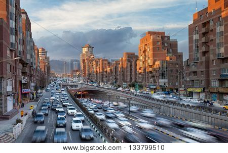 TEHRAN IRAN - FEBRUARY 19 2016: Tehran Cityscape with Cars Passing Through Tohid Tunnel in Front of Sunlit Navvab Buildings. Tohid Tunnel is the third longest urban tunnel in Middle East.