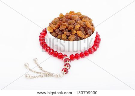 Tasty dried raisin in a white plate with a red rosay around for breakfast in Ramadan