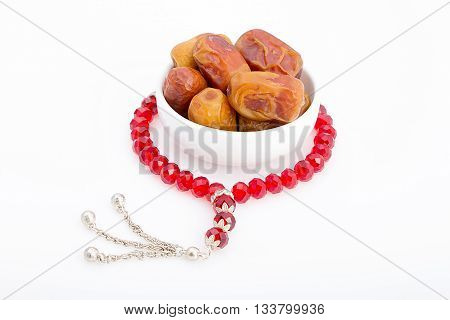 Tasty dates in a white plate with a red rosay around for breakfast in Ramadan