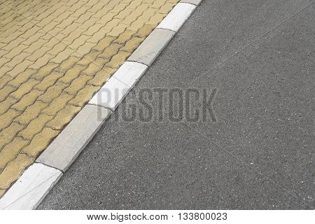 Striped border between the sidewalk and the asphalt road.