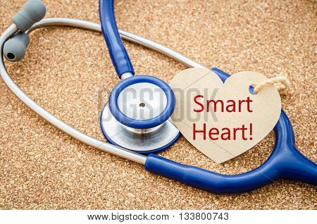 Smart heart word in paper tag with stethosope on wood table.