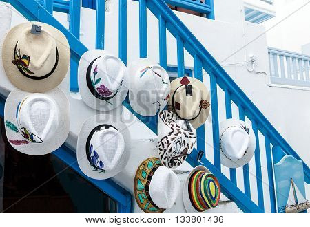 Trendy Greek summer hat collection hanging on blue banister in a typical street of Mykonos, Greek Islands