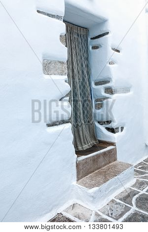 An entrance to a small white-washed house on typical street in Mykonos