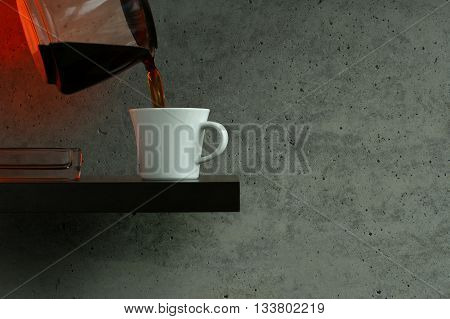 Pouring filter coffee into a white cup