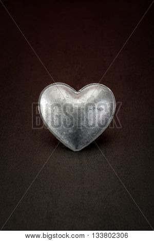 metal heart on a stone background symbolizing cold-hearted people for valentine's day