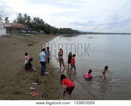 CEBU CITY, CEBU / PHILIPPINES - JULY 30, 2011: Children play in the sand and water at a public beach in Cebu.