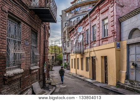 Tbilisi Georgia - April 24 2015. Woman walks on narrow street in Tbilisi