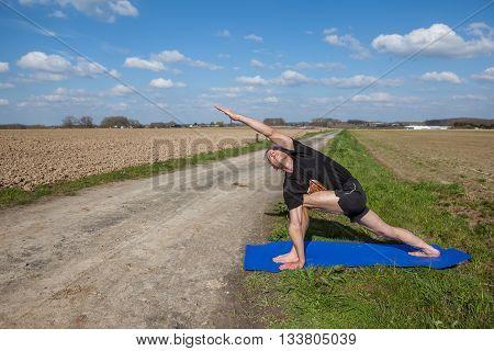 on an sunny day this man enjoys Utthita Parsvakonasana yoga in nature
